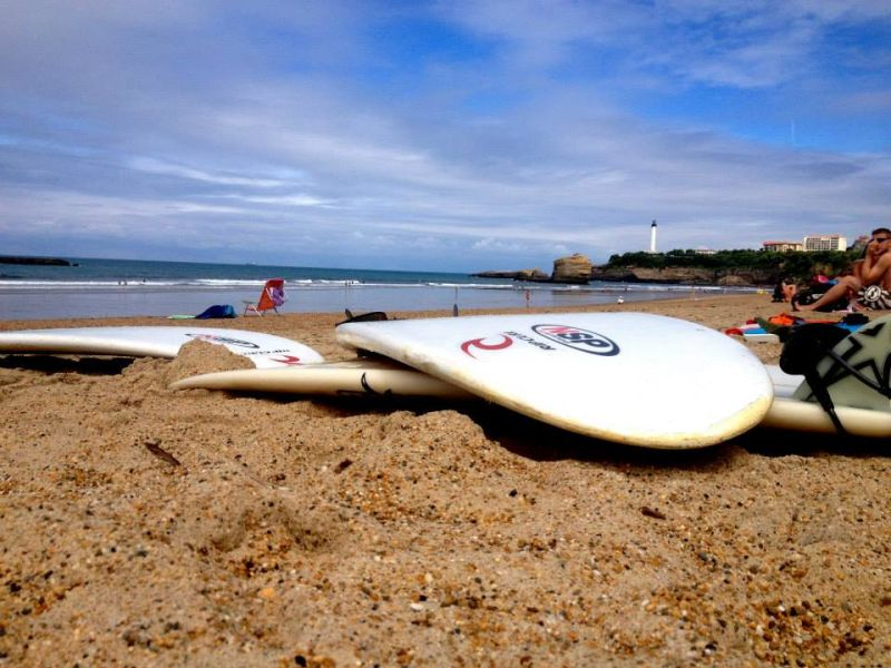 surf boards lying on the beach in Biarritz, France