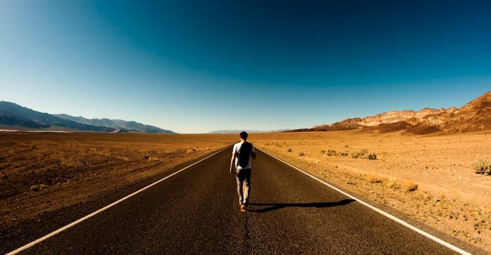 A solo traveler walking down an empty road in the desert. aTRAVELthing.com