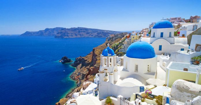 A view of the blue domed buildings of Santorini overlooking the Aegean Sea