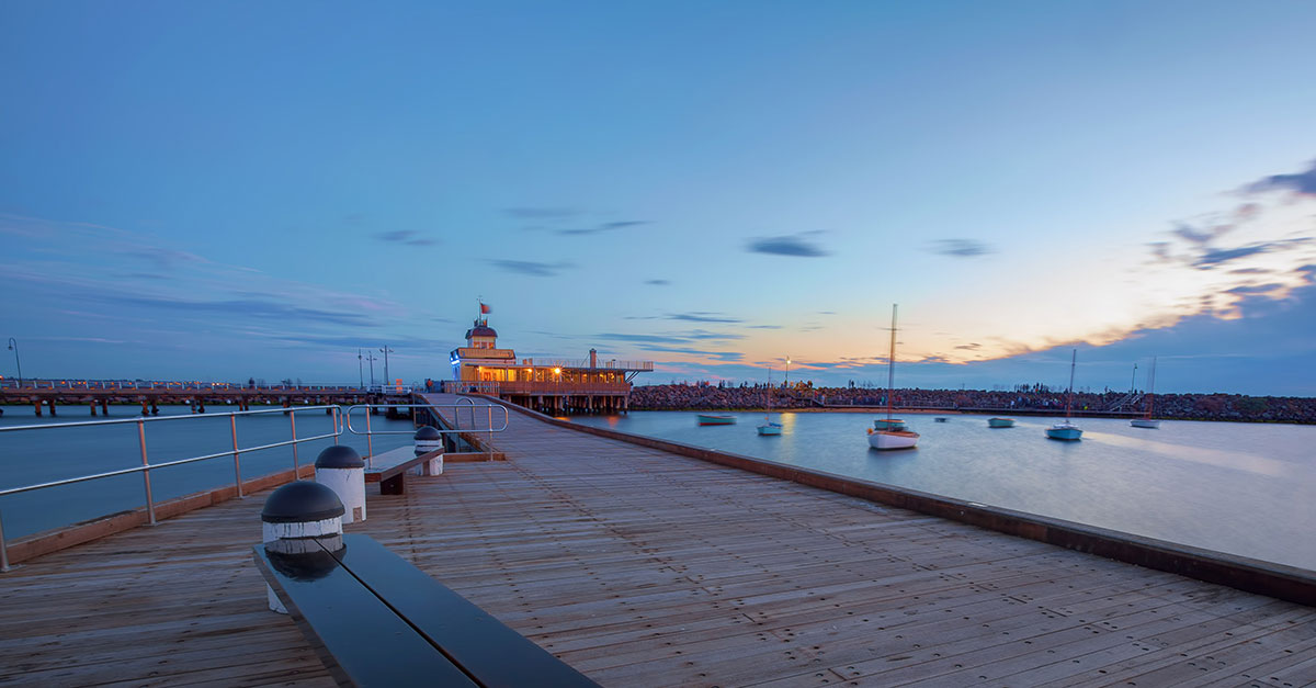 A view of the pier at St. Kilda Beach in Melbourne Australia at dusk