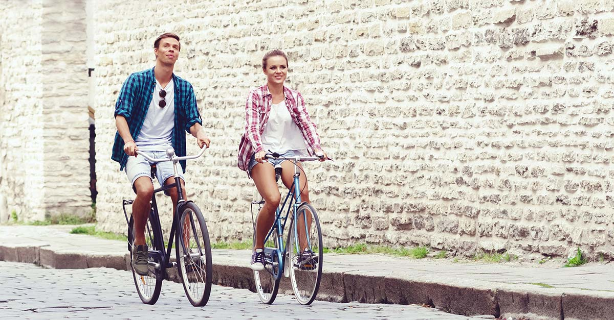Couple riding bicycles in an old european village