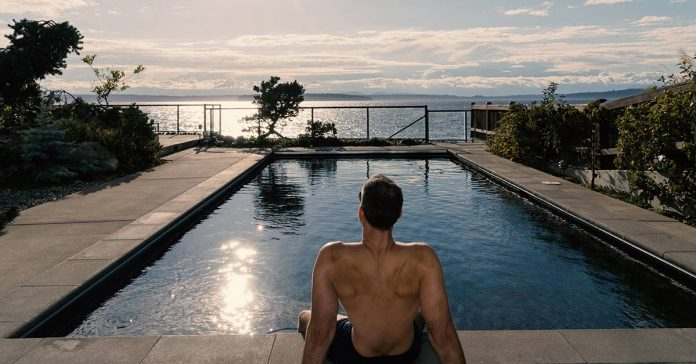 Athletic man sitting by a pool while on vacation