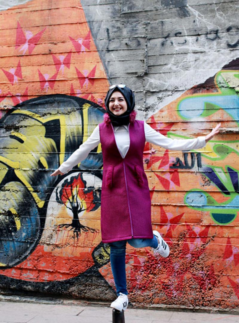 A woman wearing a hijab on the street with street art in the background