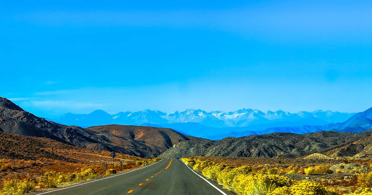 image of an empty road with mountains in the background