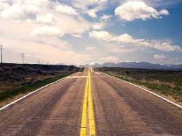 Image of an open road with blue skies and clouds in the background