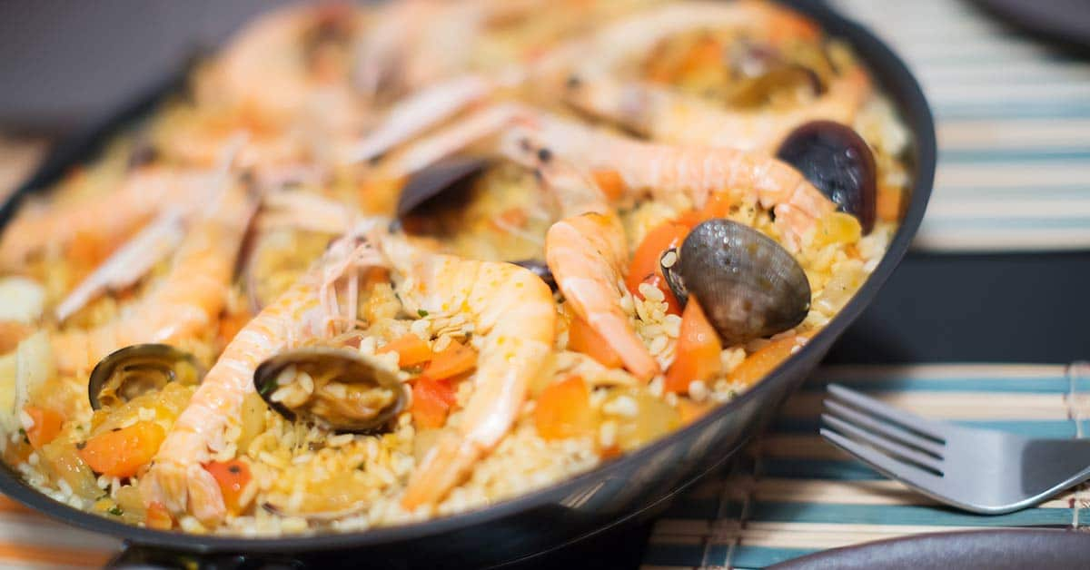 a serving dish with Paella in it