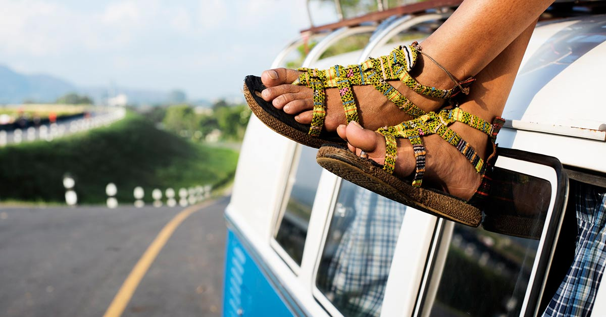 a person sitting on a travel van with their feet hanging off the edge
