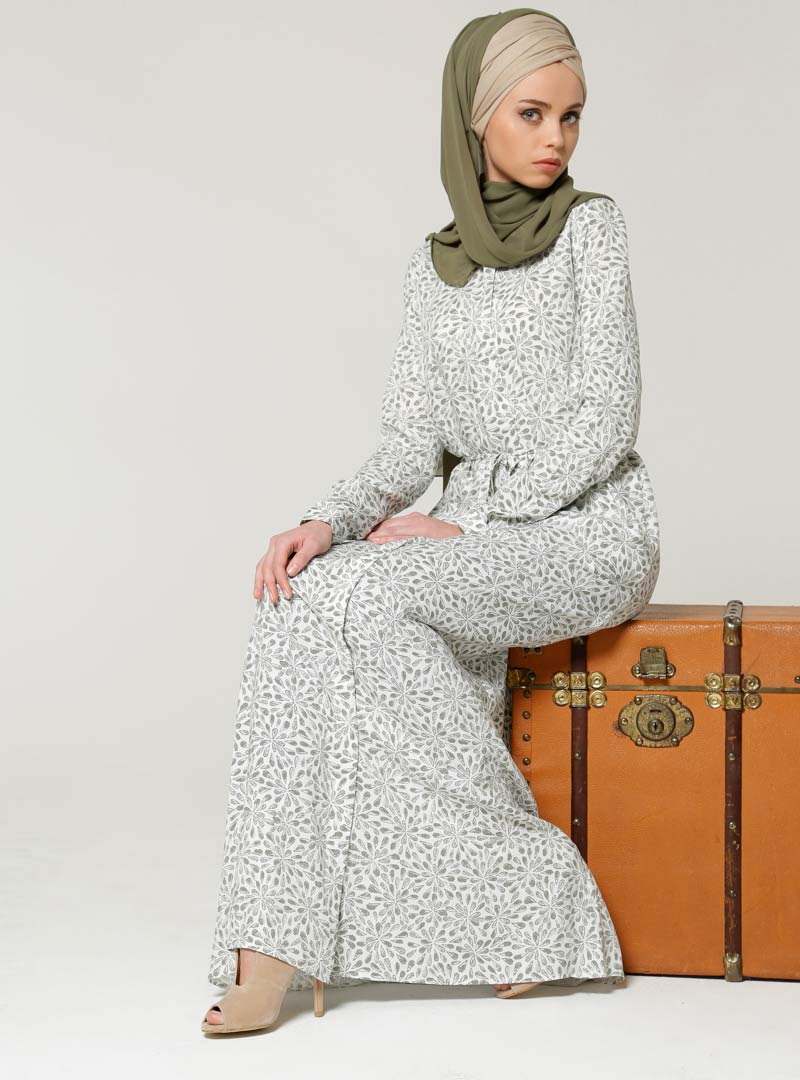 Woman wearing a hijab while sitting on a suitcase