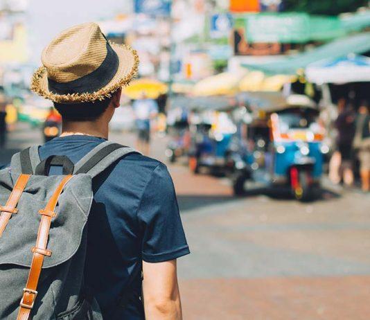 Male backpacker walking down a street in Southeast Asia