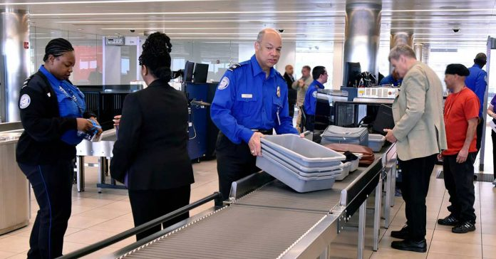 TSA officers at a security checkpoint in an airport