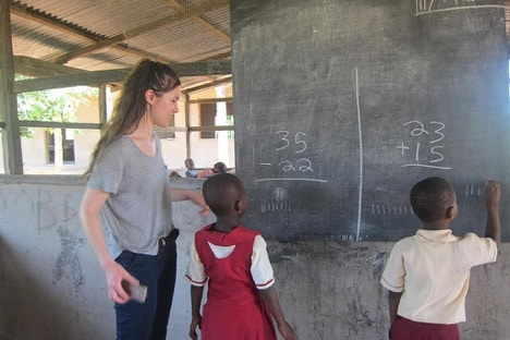 A pay to work volunteer teaches two children to solve a math problem
