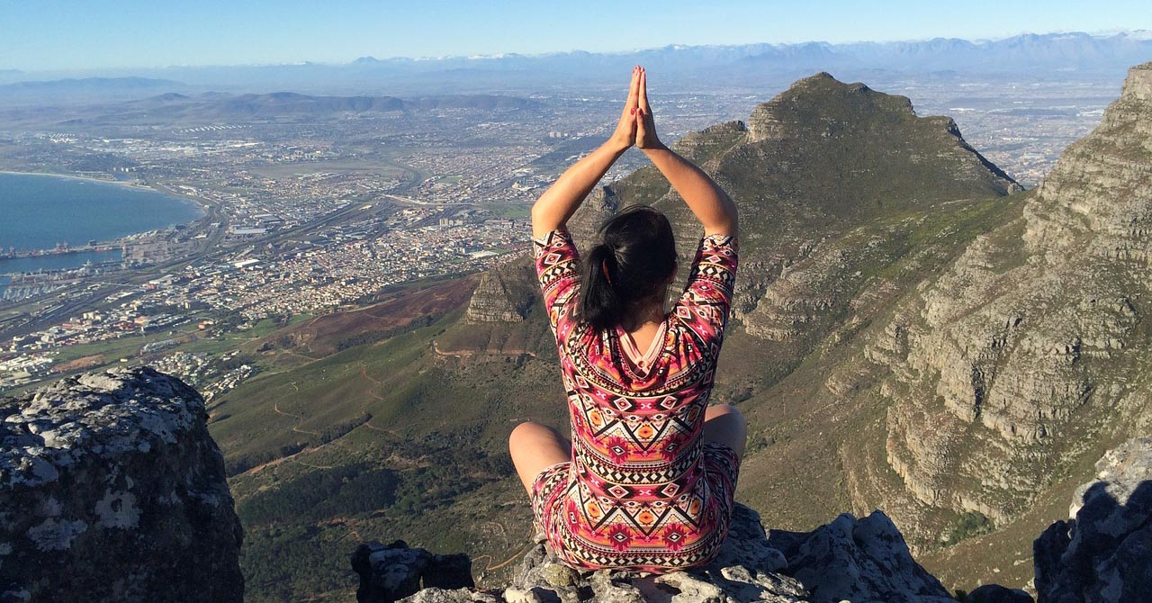 A woman doing yoga high on a mountain in Cape Town South Africa