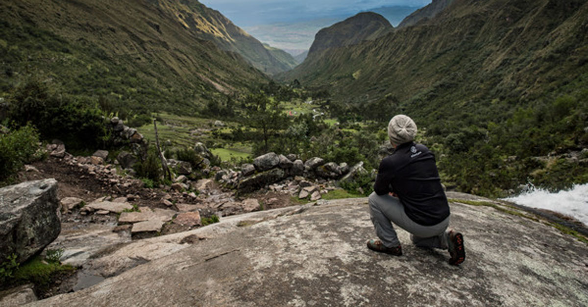 A hiker in Peru looking out a deep valley