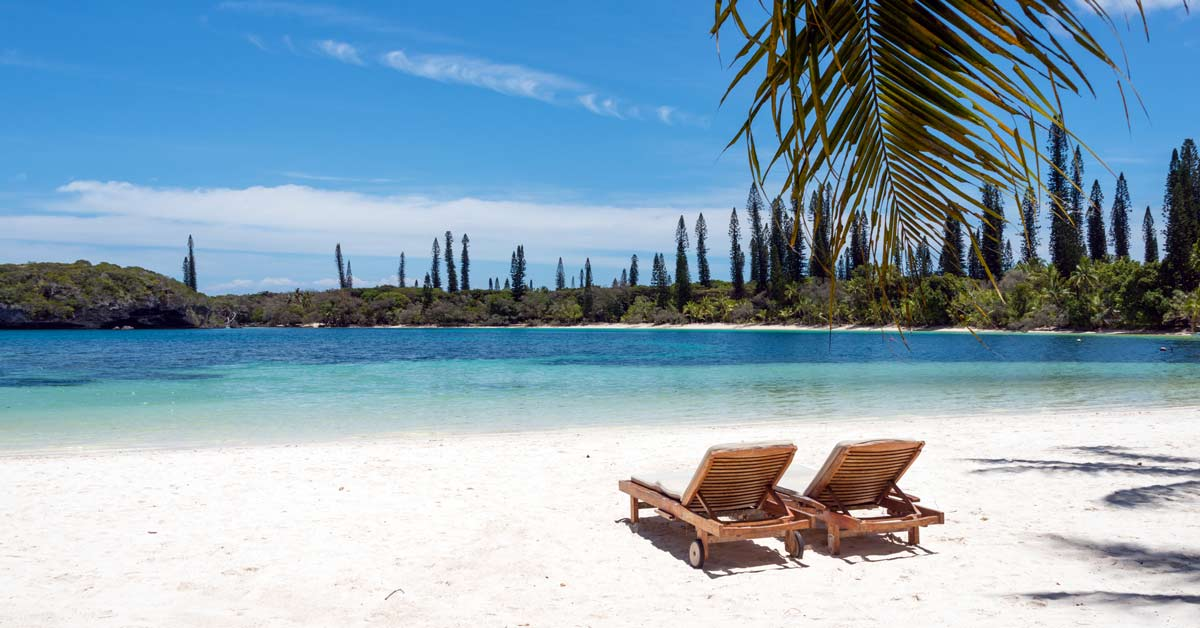 A beach with two lounge chairs in New Caledonia