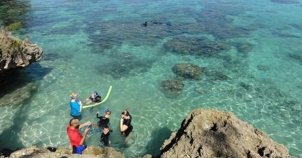 A family snorkeling on rocky beach in Lifou, New Caledonia