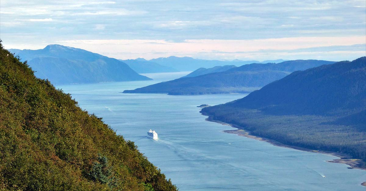 A cruise ship sailing through a fjord in Alaska. www.aTRAVELthing.com