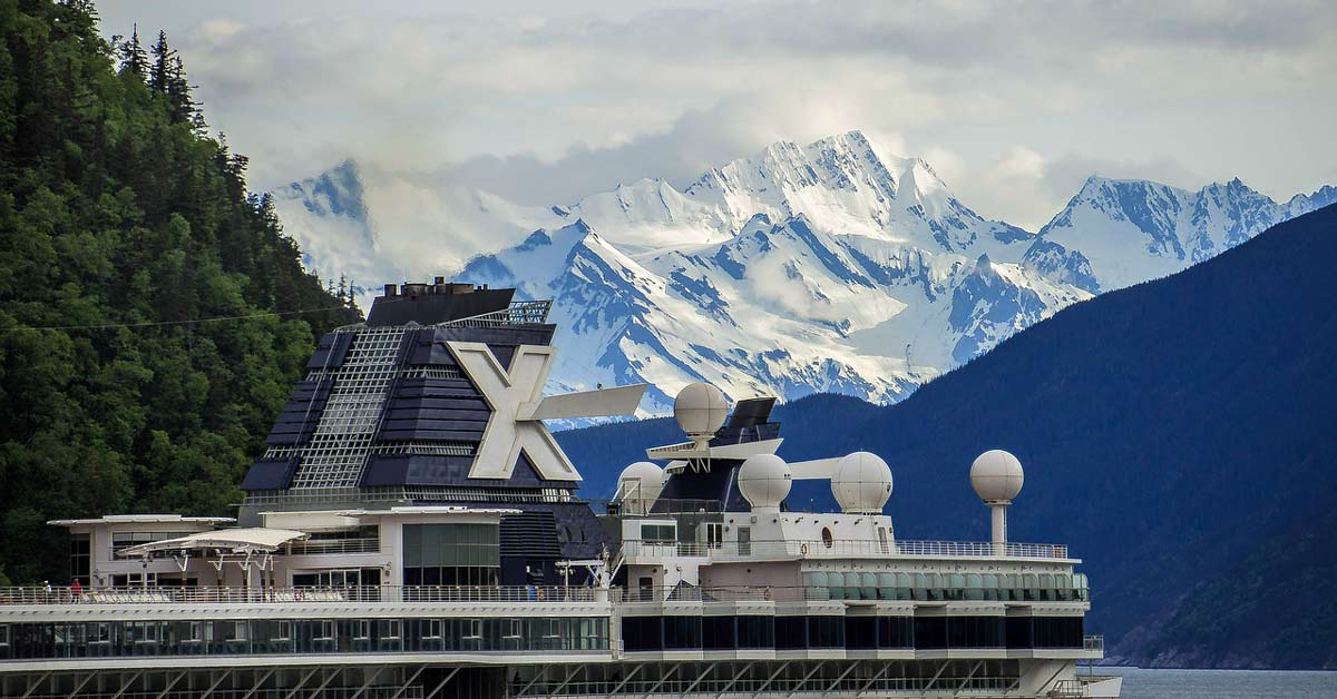 A large cruise ship in Alaska with snow topped mountains in the background. www.aTRAVELthing.com