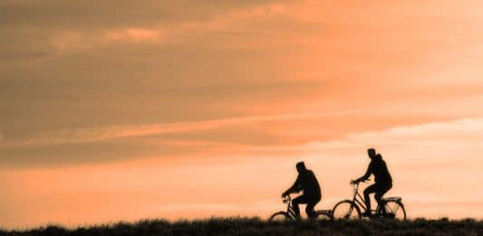 A couple of travelers biking at sunset on an Australian cycling trail. www.aTRAVELthing.com