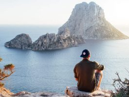 A slow traveler sitting on a cliff experiencing the view of the ocean. aTRAVELthing.com