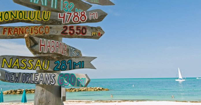 Sign post on beach in Key West Florida pointing to many destinations. aTRAVELthing.com
