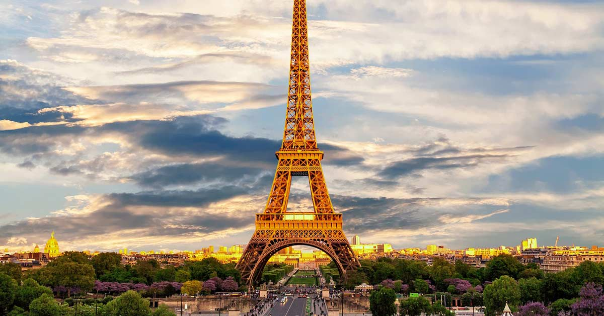 A view of the Eiffel Tower in Paris France during a summer sunrise. www.aTRAVELthing.com