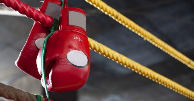 A pair of Muay Thai boxing gloves hanging off the ropes of a kick boxing ring. www.aTRAVELthing.com