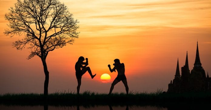 Two Muay Thai fighters sparing at sunset with a temple in the background