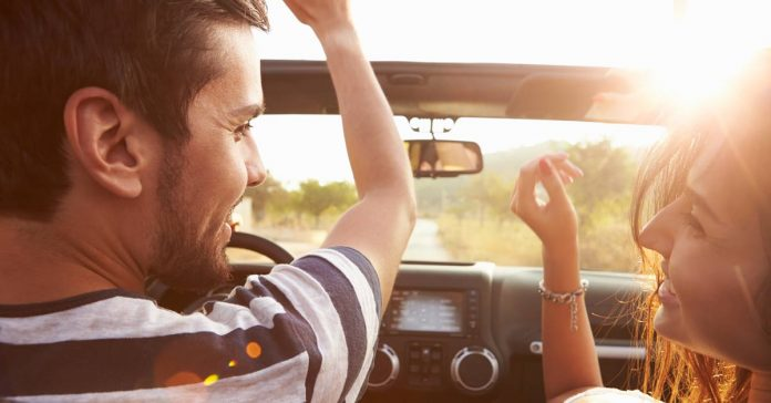 A couple enjoying music while on a road trip