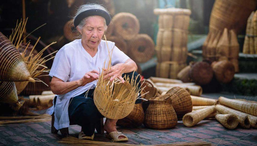An elderly asian woman weaves a basket in a remote village