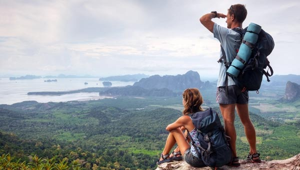 A man and woman enjoying the view from a mountain top.