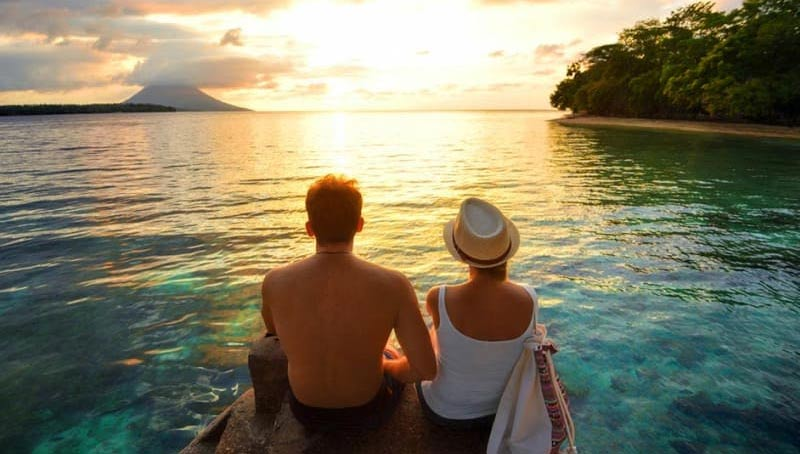 A couple enjoying a sunset while sitting on a beach