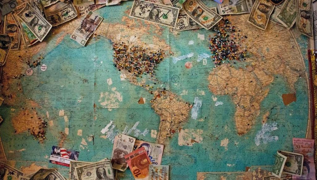 Map of the world with money laying on it.