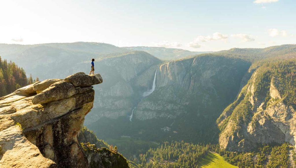 A hiker looking over a cliff in Yosemite National Park in California.