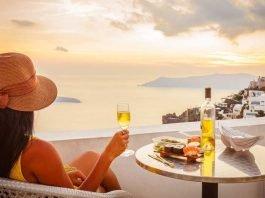 Female tourist enjoying food, wine and sunset view at Santorini, Greece