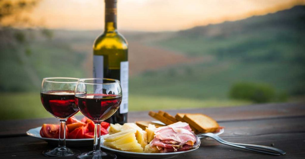 Still life of red wine ,cheese and prosciutto in rural Italy.