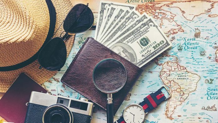 An image of a wallet full of money and a map for travel